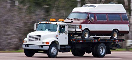 RV towed by a flatbed tow truck
