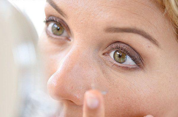 Woman putting eye lenses on